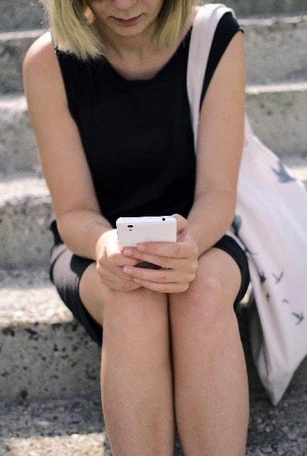 iphoneとそれを見る女性