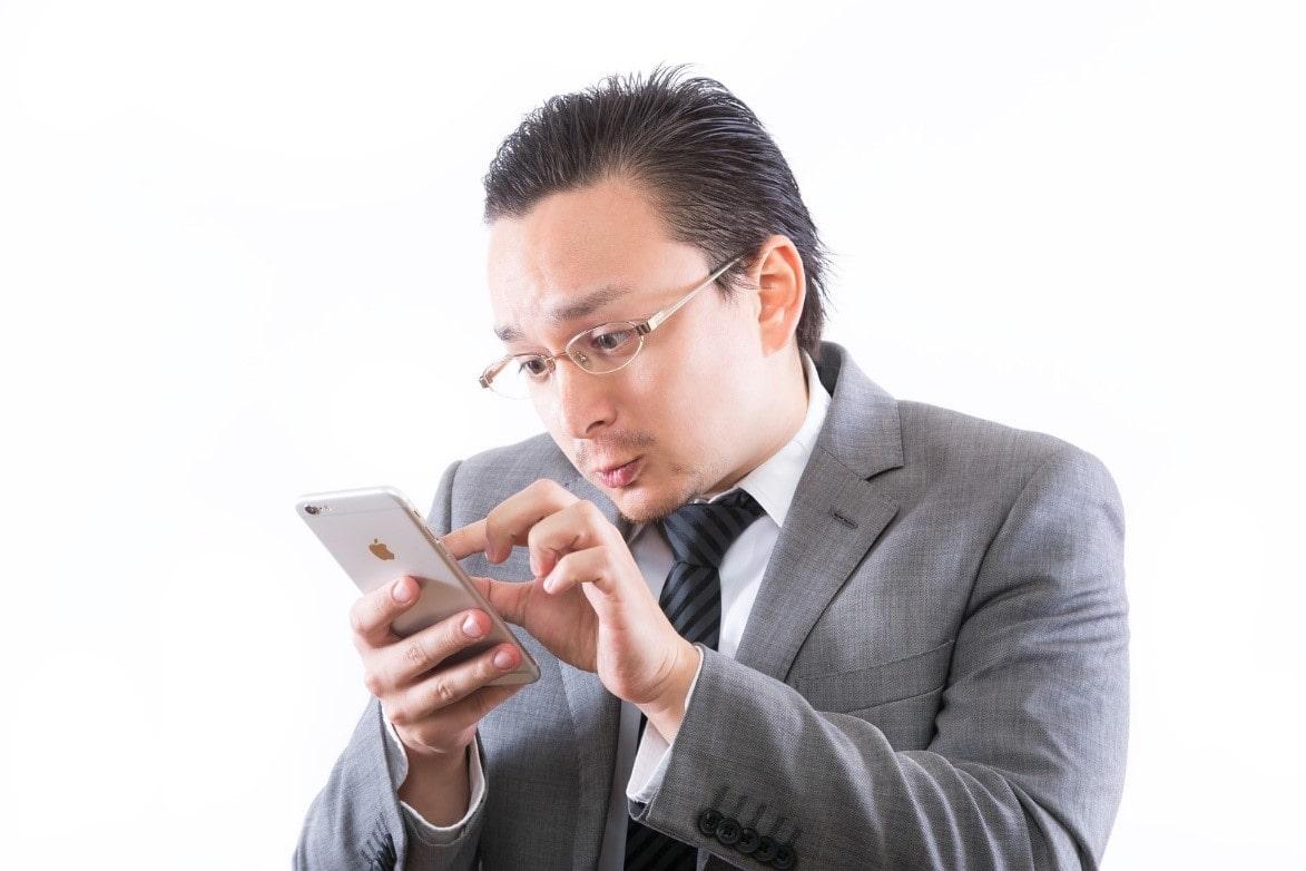 サラリーマンが携帯を見つめる
